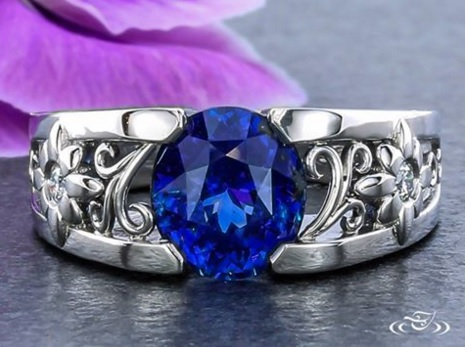 A stunning sapphire surrounded by diamond flowers and delicate filigree curls. At Green Lake Jewelry Works