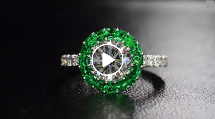 """Bez Ambar's beautiful """"Ring of Fire"""" featuring stunningly vivid green emeralds surrounding a round brilliant diamond center mounted on a pavé encrusted platinum shank."""